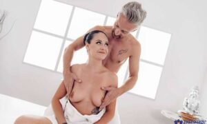 Masseur pours oil down her chest